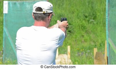 Man shoot with a gun in targets on shooting range....