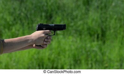 pistol shooting on green background, grass outside