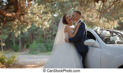Bride and groom pose near the car in pine wood - Bride and...