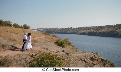 Bride and groom walking on the rocks above the river....