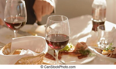 Plate with food and glass of red wine on the table - Plates...