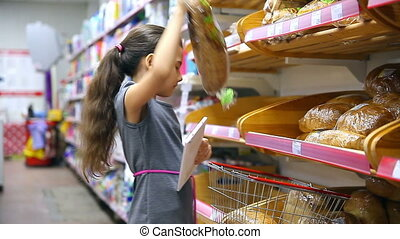 girl teen from tablet with in supermarket to buy baking bread food