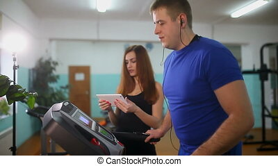 man on treadmill in the gym Girl on the treadmill trainer, sports a healthy lifestyle