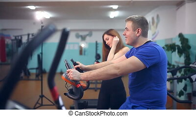man on a stationary bike in the gym laughs - man on a...