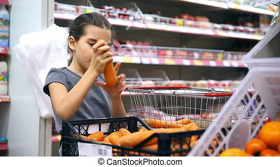 girl teen with in supermarket to buy food carrot vegetables...