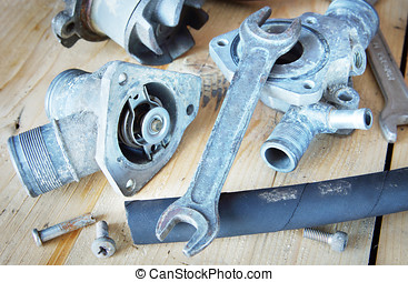 Various automobile motor spare parts lie on the wooden workbench