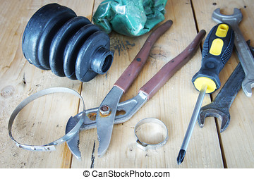 Automobile spare parts. Rubber protective case and instruments lie on the wooden workbench in a garage