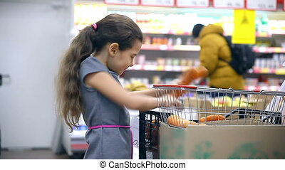 girl teen with in supermarket to buy carrot vegetables food...