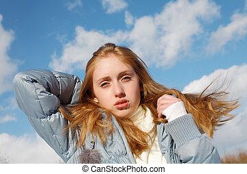 girl in jacket on blue sky background