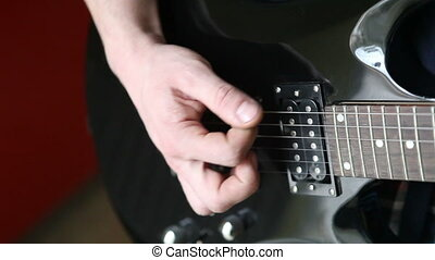 man playing mediator the electric guitar close-up