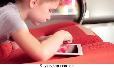 little boy playing on the tablet computer games