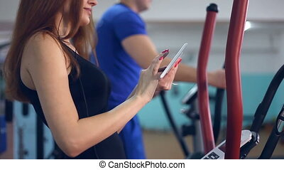 girl with tablet sports man trainer ellipsoid on simulator...