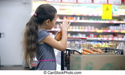girl teen with in supermarket to buy carrot food vegetables