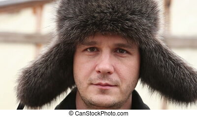 man in winter fur hat looks into the camera