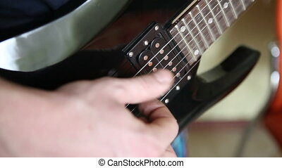 man playing the electric guitar brute force, close-up