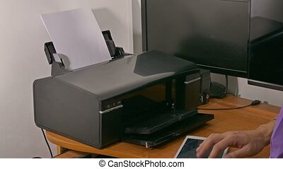 man businessman in office prints documents on printer