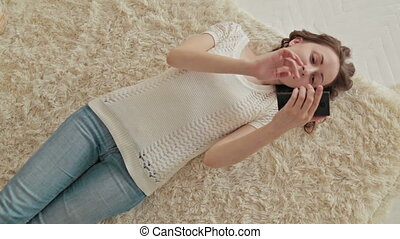 Woman lying down on the bed using her cellphone. - A...
