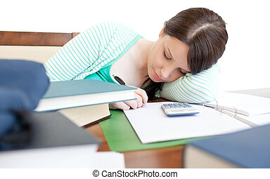 Young tired woman studying on a table in the living-room