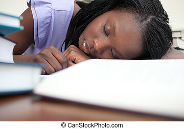 Exhausted woman sleeping while studying at home