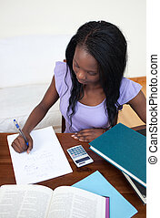 Concentrated Afro-American teen girl doing her homework at...