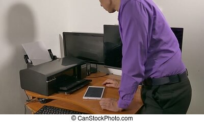 businessman in the office prints documents on the printer -...