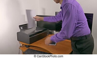 businessman in office prints documents on the printer -...