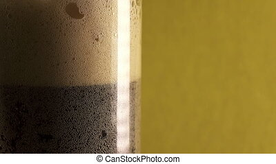 The brown foaming drink kvass or beer is poured in a glass,...