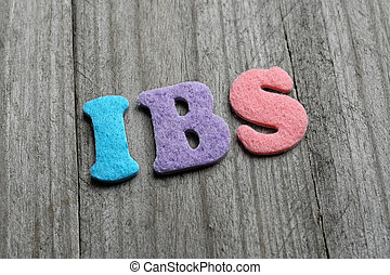 IBS Irritable Bowel Syndrome acronym on wooden background