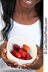 Afro-american a woman holding a bowl of strawberries