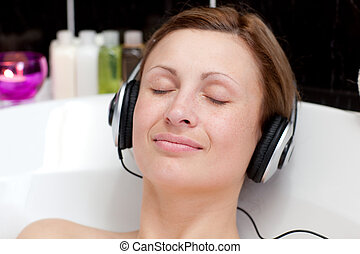 Close-up of a relaxed young woman listening music with...