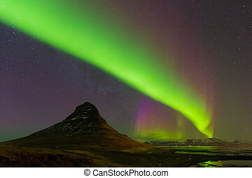 Aurora dancing over Kirkjufell mountain with fully of start...