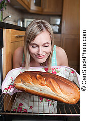 Delighted blond woman baking bread in a kitchen