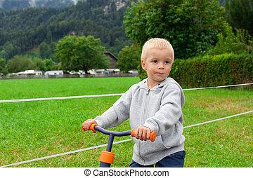 Little boy riding a bike.