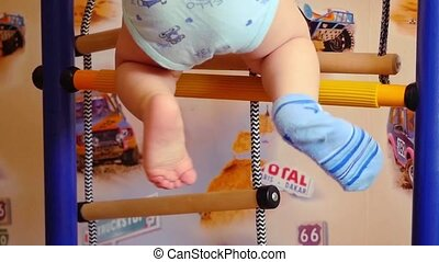 baby is engaged in a sports training apparatus at home in...