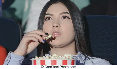 Asian girl with a bucket of popcorn