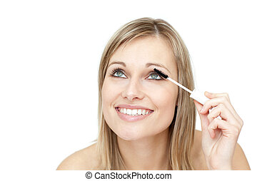 Bright woman putting mascara against a white background