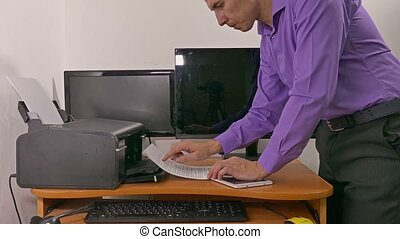 man businessman in office prints examines documents on...