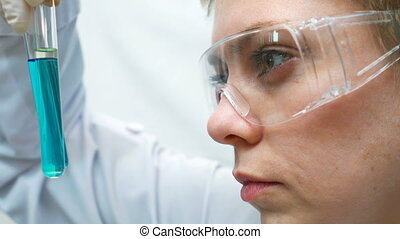 Doctor scientist looking at the test tubes in lab - Lab...