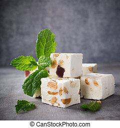 Soft nougat blocks with peanuts and fruit with fresh mint...