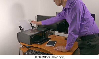 businessman in office prints documents on printer -...
