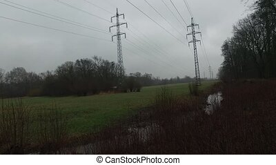 Electricity Pylons - Electricity pylons on meadow during...