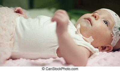Happy baby girl lying on pink blanket