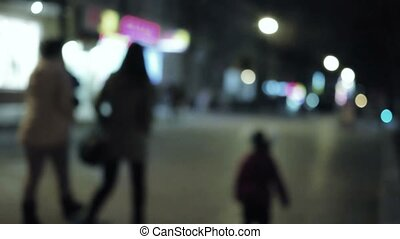 Pedestrians with small boy crosswalk in city at night St...