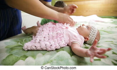 Mom putting dress on her little baby girl