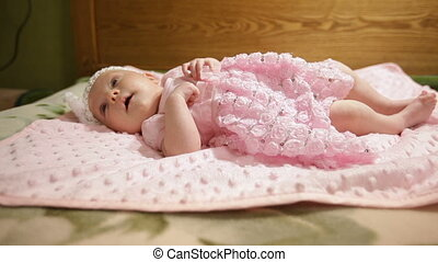 Happy baby girl lying on pink blanket