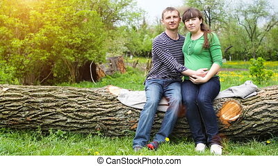 Loving couple in summer park sitting on tree