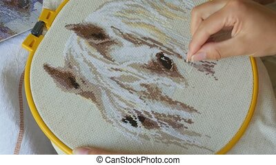 Embroidery cross stitching - Woman hands doing cross-stitch...