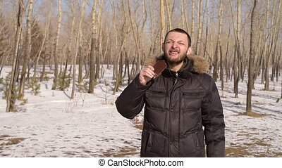 Man eating chocolate in the forest - Man eating a chocolate...