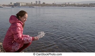 Woman dropping piece of ice into river