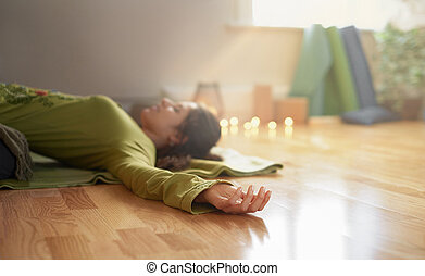 Attractive mixed race woman doing restorative yoga - Serene...